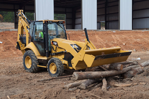 A CAT 416F Backhoe Loader moving logs for a construction operation.