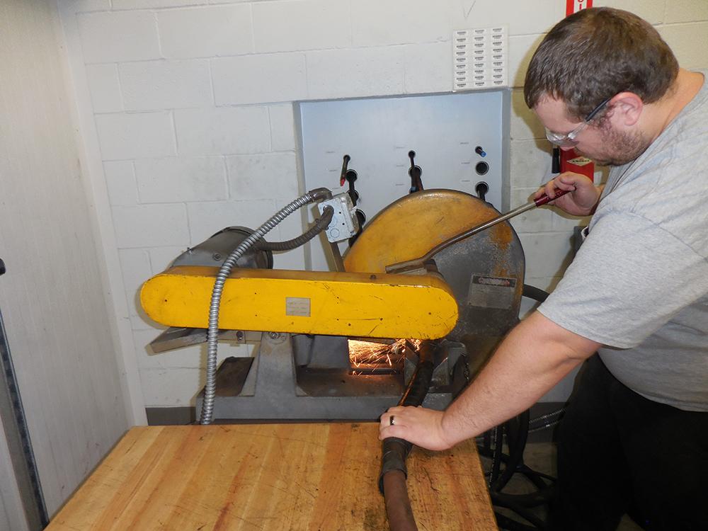CB HYMAC technician repairing a hydraulic hose